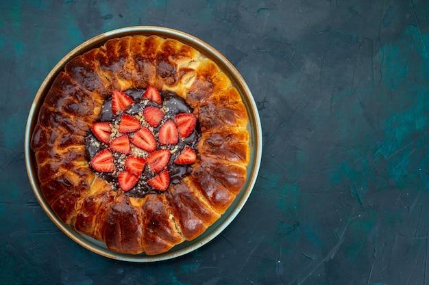 Widok z góry na ciasto truskawkowe z dżemem i świeże czerwone truskawki na niebieskiej powierzchni