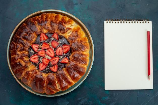 Widok z góry na ciasto truskawkowe z dżemem i świeżymi truskawkami na niebieskiej powierzchni