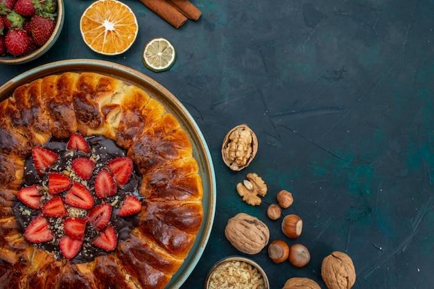 Widok z góry na ciasto truskawkowe z orzechami i cynamonem na niebieskim biurku