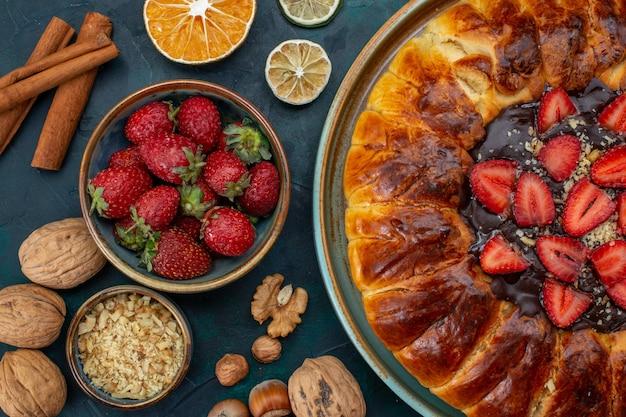 Widok z góry na ciasto truskawkowe z orzechami i laskami cynamonu
