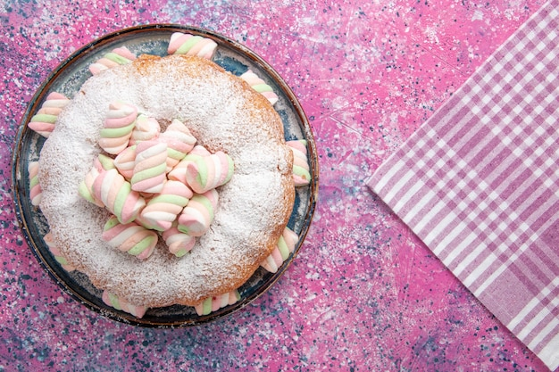 Widok z góry na ciasto w proszku z cukrem z piankami na różowej powierzchni
