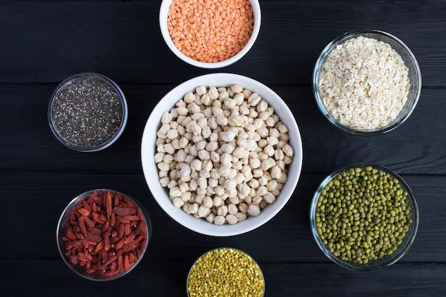 Widok z góry na ciecierzycę, płatki zbożowe, jagody goji, nasiona chia, zacier, czerwoną soczewicę i pyłek pszczeli w miseczkach