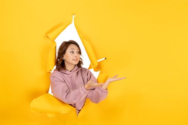 Widok z góry na ciekawą kobietę patrzącą na coś po lewej stronie i wolne miejsce na żółtym podartym