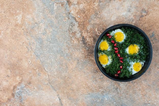 Widok z góry na ciemną patelnię z omletem i zieleniną