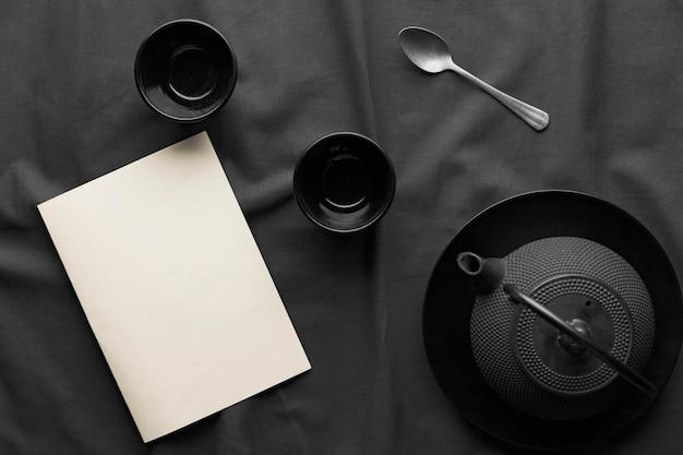 Widok z góry na ciemne miski z czajnikiem i łyżką