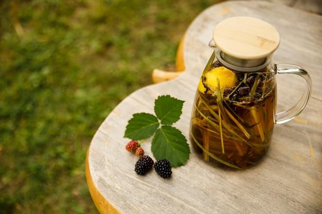 Widok z góry na ciepły szklany czajniczek, liście zielonej herbaty i trawę cytrynową na drewnianym biurku w jesienny dzień. zbliżenie obrazu.