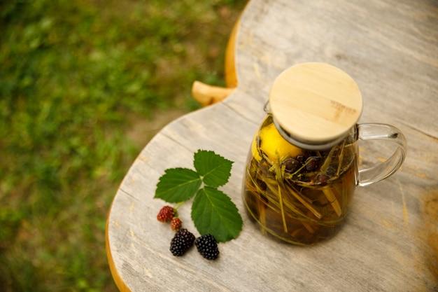 Widok z góry na ciepły szklany czajniczek, liście zielonej herbaty i trawy cytrynowej na drewnianym biurku w jesienny dzień.
