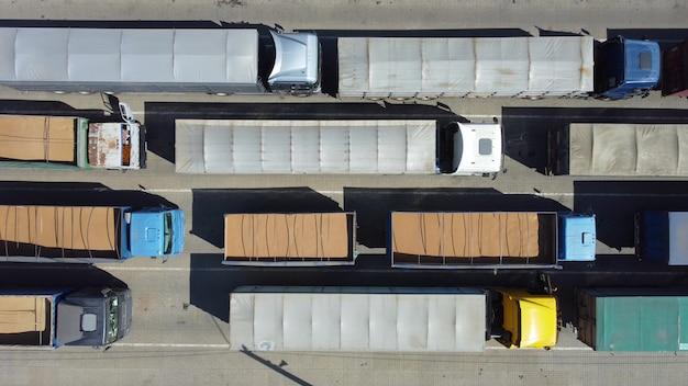 Widok z góry na ciężarówki stojące w kolejce przy terminalu z bliska. transport ładunków ciągnikami. transport logistyczny na parkingu.