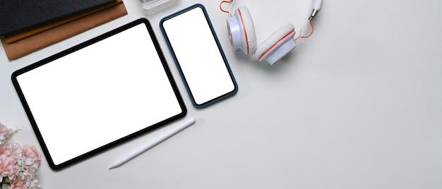 Widok z góry na cyfrowy tablet, telefon komórkowy, słuchawki i miejsce na kopię
