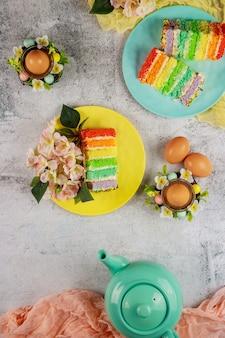 Widok z góry na czajniczek z kawałkiem kolorowego ciasta i brązowymi jajkami na przyjęcie wielkanocne