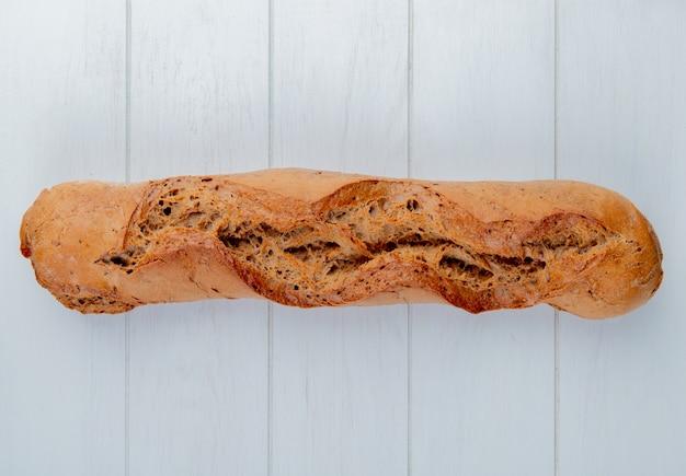 Widok z góry na czarną bagietkę po lewej stronie i drewniane tło z miejsca na kopię