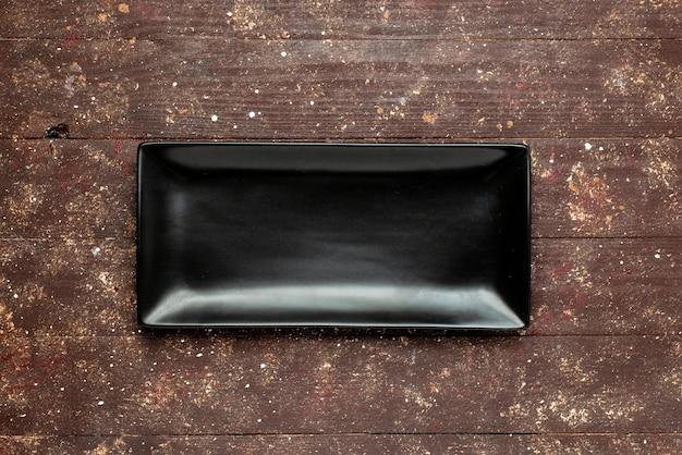 Widok z góry na czarną pustą formę do ciasta na brązowym rustykalnym drewnianym, piecu do pieczenia drewna