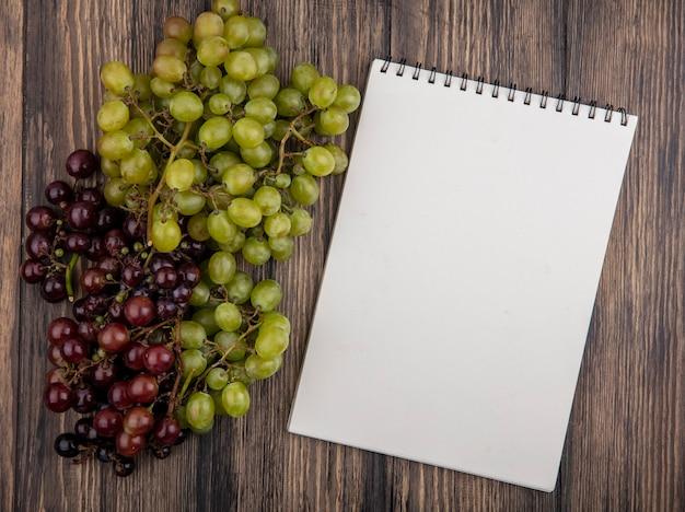 Widok z góry na czarne i białe winogrona i notes na podłoże drewniane z miejsca na kopię