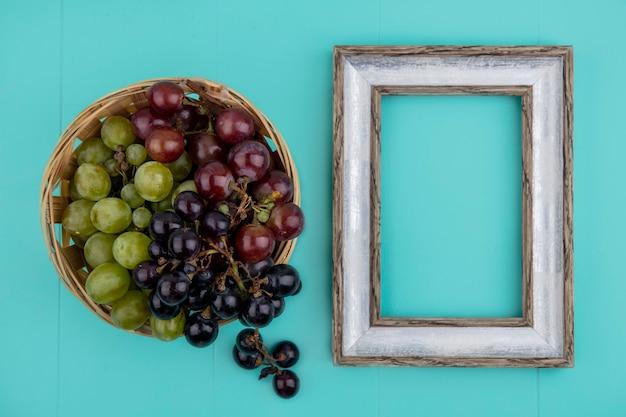 Widok z góry na czarne i białe winogrona w koszu z ramą na niebieskim tle z miejsca na kopię