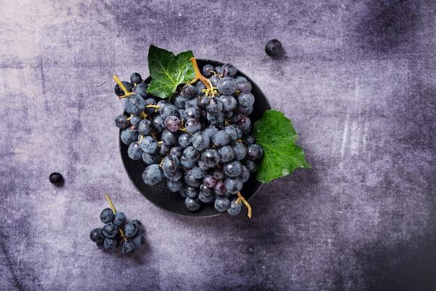 Widok z góry na czarne winogrona z zielonymi liśćmi