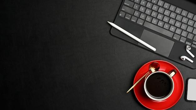 Widok z góry na czarny obszar roboczy koncepcja z klawiaturą tabletu, filiżanką kawy, akcesoriami i miejscem na kopię