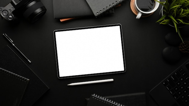 Widok z góry na czarny stół z materiałami do tabletu i dekoracjami w pokoju biurowym