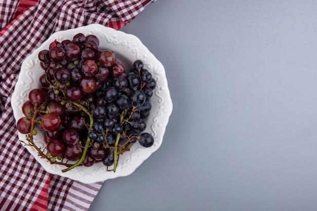 Widok z góry na czarny winogron w talerzu na kratę szmatką na szarym tle z miejsca na kopię