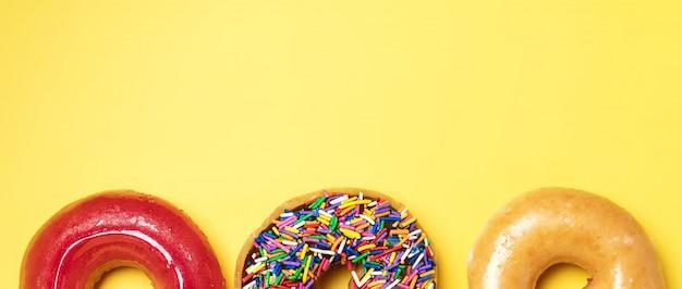 Widok z góry na czekoladowy mrożony pączek z posypką, lukrowany pączek z lukrem cukrowym i truskawkowy pączek na żółtym tle.