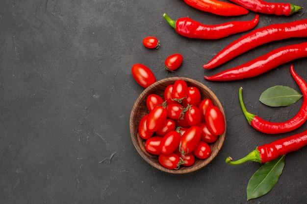 Widok z góry na czerwoną paprykę i liście płatne oraz miskę pomidorków koktajlowych po prawej stronie czarnego stołu z miejscem na kopię