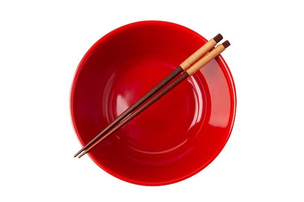 Widok z góry na czerwoną pustą miskę i pałeczki są umieszczone na górze miski na białym tle.