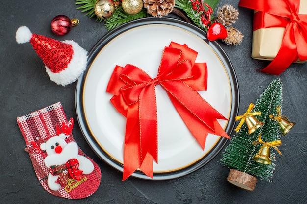 Widok z góry na czerwoną wstążkę w kształcie łuku na talerzu obiadowym choinka gałęzie jodły szyszka pudełko pudełko czapka świętego mikołaja skarpety świąteczne na czarnym tle