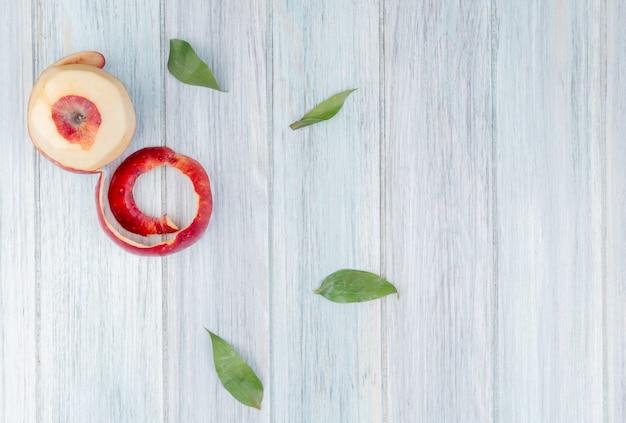 Widok z góry na czerwone jabłko i jego skorupę na podłoże drewniane ozdobione liśćmi z miejsca na kopię