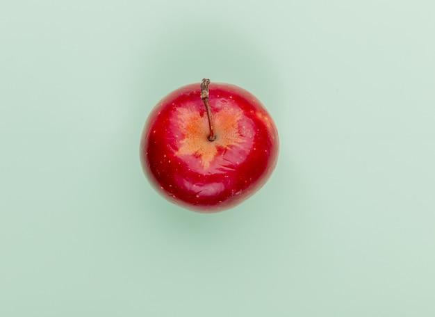 Widok z góry na czerwone jabłko na zielonym tle z miejsca na kopię