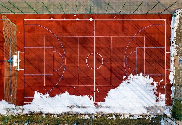 Widok z góry na czerwonym tle pola do koszykówki, siatkówki lub piłki nożnej, fotografia dronów.