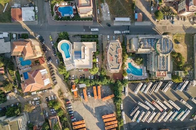 Widok z góry na dachy hoteli, ulice z zaparkowanymi samochodami i baseny z błękitną wodą w kurorcie w pobliżu morza.