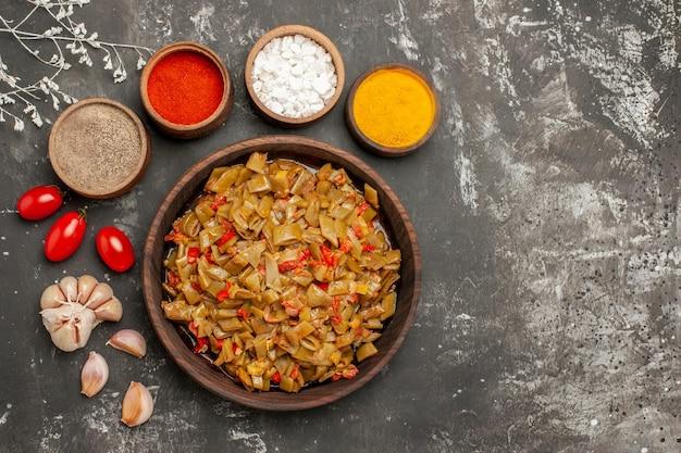 Widok z góry na danie z fasoli miski przypraw i czosnku wokół talerza zielonej fasoli z pomidorami na czarnym stole