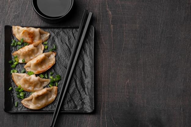 Widok z góry na danie z pierogami azjatyckimi na łupku z miejsca na kopię