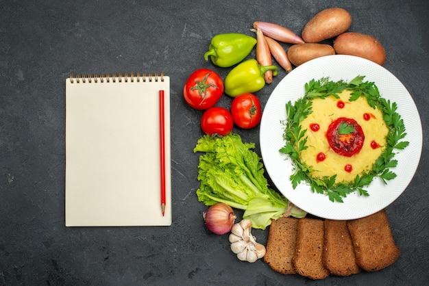 Widok z góry na danie z puree ziemniaczanym z ciemnymi bochenkami chleba i warzywami na ciemnym