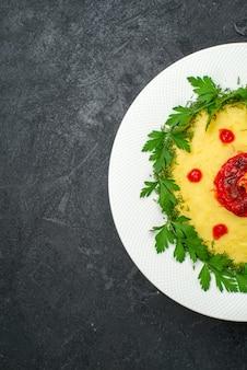 Widok z góry na danie z puree ziemniaczanym z sosem pomidorowym i zieleniną na ciemnej podłodze danie obiadowe z ziemniakami