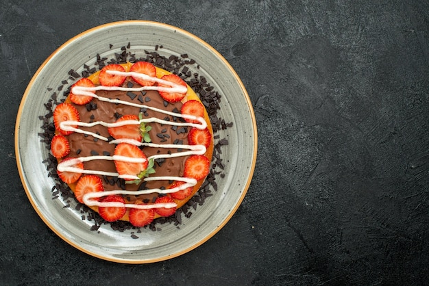 Widok z góry na deser apetyczny placek z kawałkami truskawek i czekoladą na białym talerzu po lewej stronie ciemnego stołu