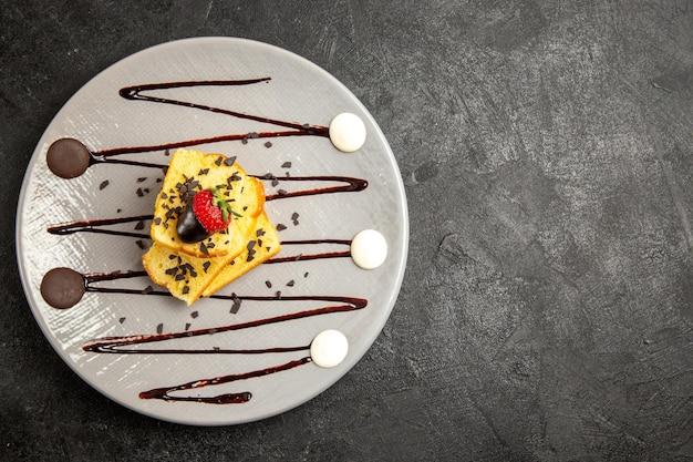 Widok z góry na deser apetyczny tort z truskawkami i sosem czekoladowym na talerzu po lewej stronie ciemnego stołu