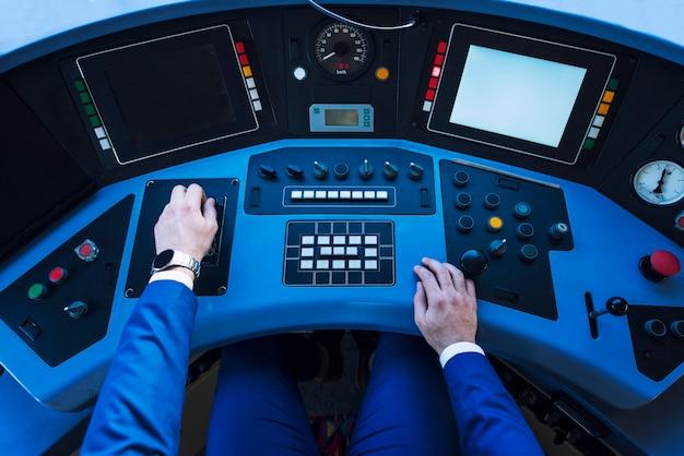 Widok z góry na deskę rozdzielczą kokpitu pociągu i ręce maszynisty podnoszące dźwignię i przyspieszające jazdę pociągiem.