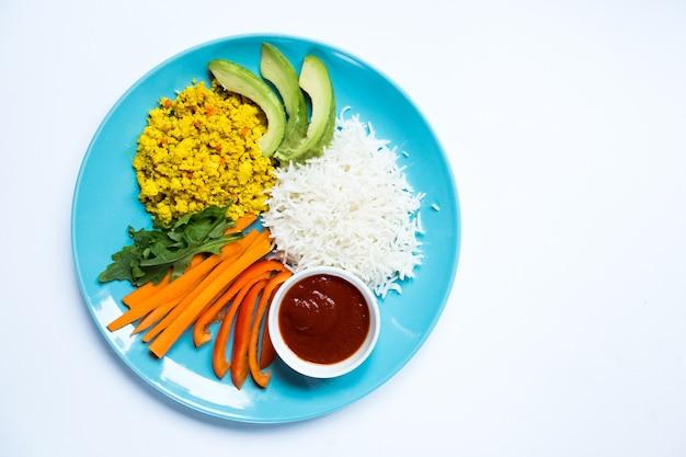 Widok z góry na dietetyczny keczup i warzywa widelcem obok niebieskiego talerza na białym tle.