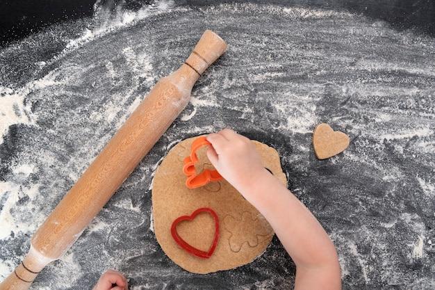 Widok z góry na dłonie dziecka z ciasta, wałkiem i ciasta