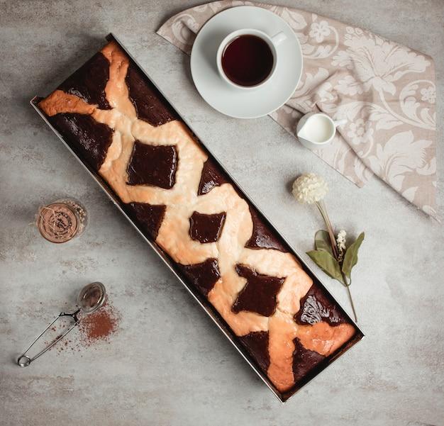 Widok z góry na długie ciasto czekoladowe podawane z herbatą