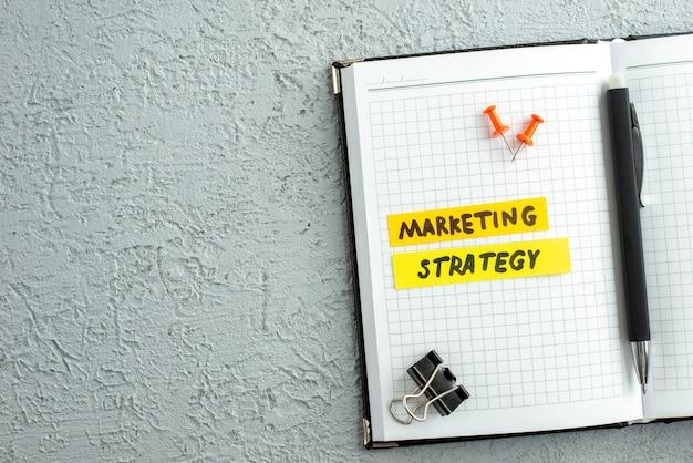 Widok z góry na długopis pisma strategii marketingowej i otwarty notatnik spiralny na szarym tle piasku
