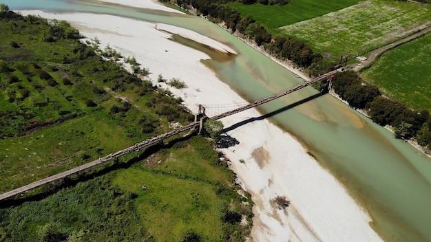 Widok z góry na dół owiec i baranów przekraczających górzystą rzekę na moście z pasterzem in