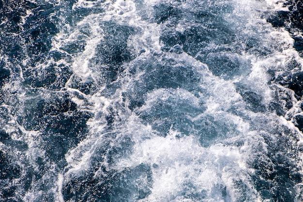 Widok z góry na dół powierzchni wody morskiej. biała piana macha teksturę jako naturalne tło.