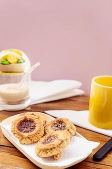Widok z góry na domowe ciasteczka maślane z dżemem, w tle nieostra cukiernica. koncepcja domowej i naturalnej żywności. orientacja pionowa. skopiuj miejsce.