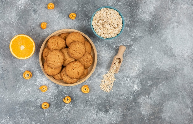 Widok z góry na domowe ciasteczka na desce i płatki owsiane z pomarańczami.