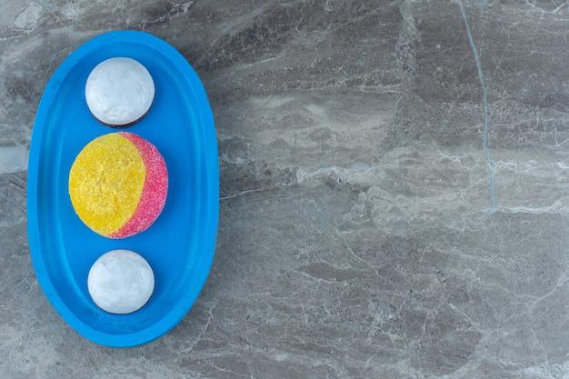 Widok z góry na domowe ciasteczka na niebieskim drewnianym talerzu.