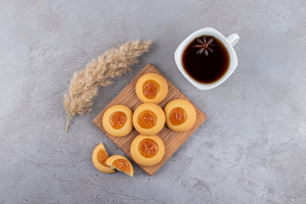 Widok z góry na domowe ciasteczka z dżemem i filiżanką herbaty.