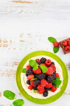 Widok z góry na domowe ciasto jagodowe ozdobione świeżymi malinami i jeżynami na białym tle.