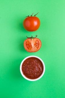 Widok z góry na domowy keczup pomidorowy i pomidor na zielonym tle. lokalizacja w pionie.