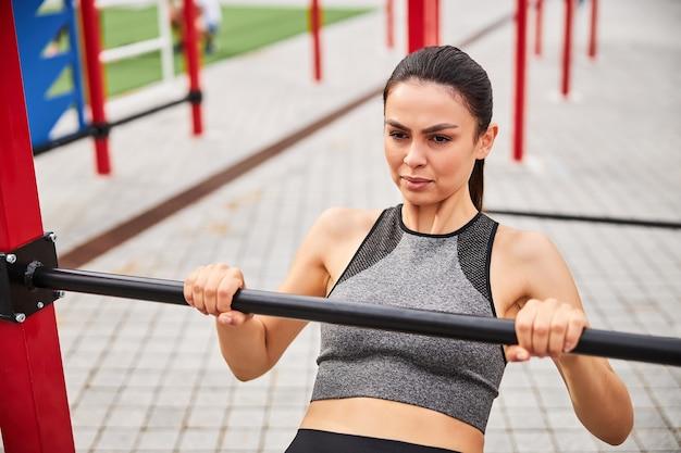 Widok z góry na dość wysportowaną kobietę wykonującą podciąganie podczas treningu na boisku sportowym na świeżym powietrzu